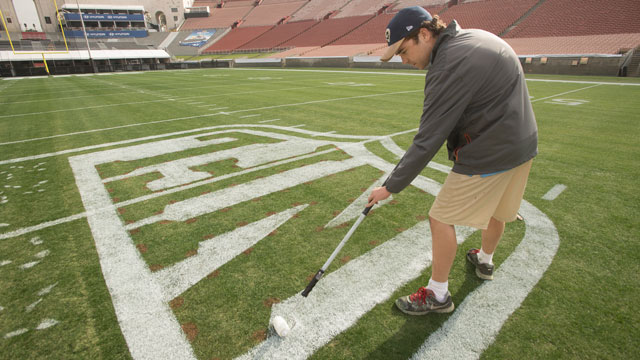 McLaughlin paints the NFL logo on the playing field at the Los Angeles Coliseum in preparation for the Rams game against the Atlanta Falcons.