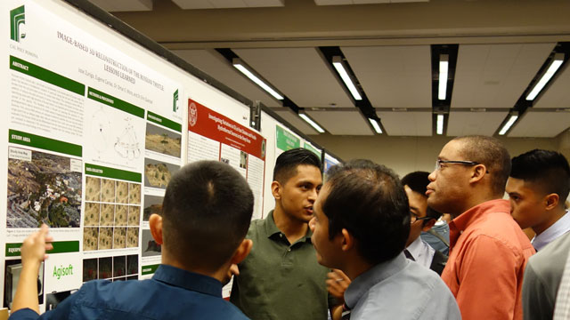 Participants at the 24th Annual Southern California Conferences for Undergraduate Research at UC Riverside examine a poster presentation by a Cal Poly Pomona student.
