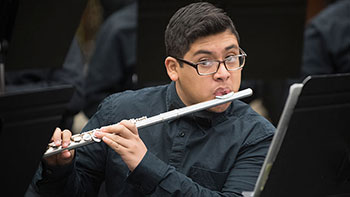 Student plays the flute during the recording of a music video at Gary High School.
