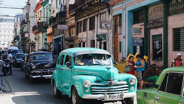 Vintage cars maneuver through a colorful street in Havana.