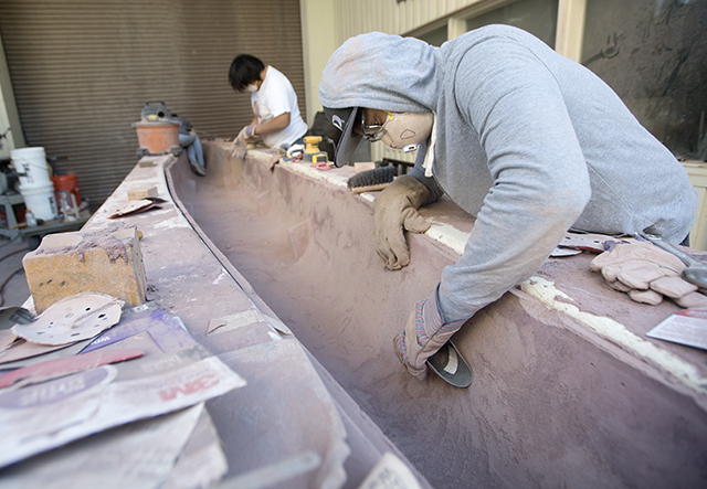 Daryl Frigillana sands the inside of this year's concrete canoe at the team's lab at Cal Poly Pomona.
