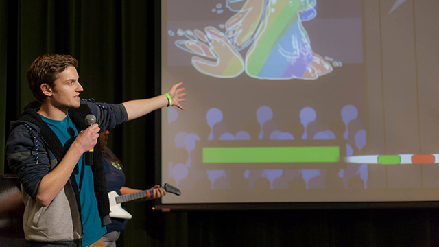 Colin Trotter presents Battle of the Bards, a role-playing video game that uses a guitar-shaped controller, at the 24-hour Hackpoly competition. The Battle of the Bards entry was the top-finishing all-Bronco team.
