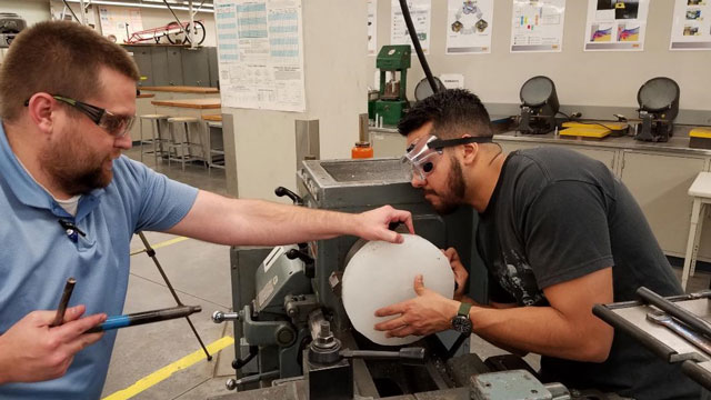 Cal Poly Pomona engineering students practice using a lathe, a machine used to shape metal, wood and other materials.