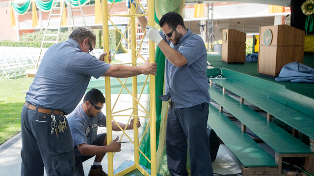Workers install a tower on the Commencement stage for the start of three days of ceremonies in the University Quad.