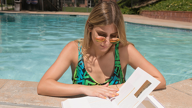A female student reading a book by the pool