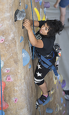 Aisha Saleemi, a zoology major, climbs Bronco Peak, the climbing wall at the BRIC at Cal Poly Pomona.