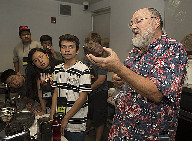 BioTrek Curator Mike Brown shows Upward Bound students a cacoa pod at BioTrek. Brown taught the recent high school grads how to make chocolate.