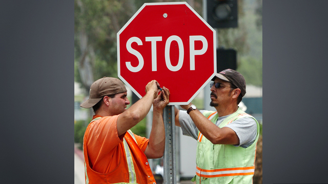 Two workers installing a stop sign