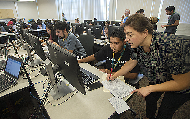 Biology Major Carlos Arias gets some help registering for classes from Monica Montes, a faculty member in the Biological Sciences Department, during Transfer Student Orientation at Cal Poly Pomona.