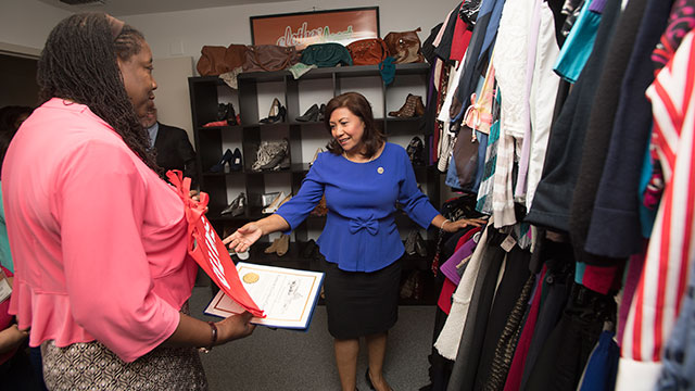Congresswoman Norma Torres looks at clothes with Cheryl Love, career counselor, in the Career Center's Clothes Closet.