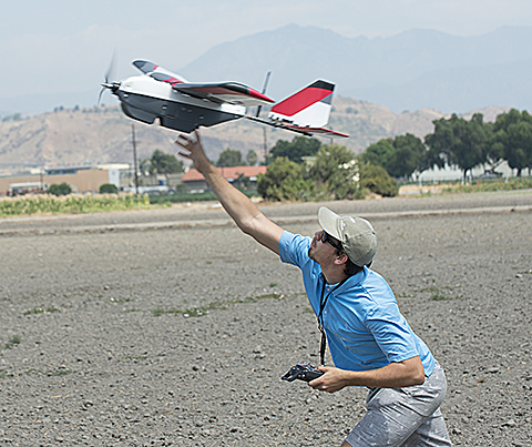 Tristan Sherman, an Aerospace Engineering junior, launches a research aircraft used  to do imaging of citrus crops at Spadra Ranch near Cal Poly Pomona.