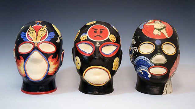 "Zengo Yoshida's ""1-SuperHeros, 1-EmojAttack, 1-Manga (comic) Invasion"" from the Pro Wrestler Masks for Millennials & Generation Z Series; porcelain slip cast, underglaze paint, cone 6 glaze now on display at the Kellogg Gallery in the Ink & Clay 43 exhibit."
