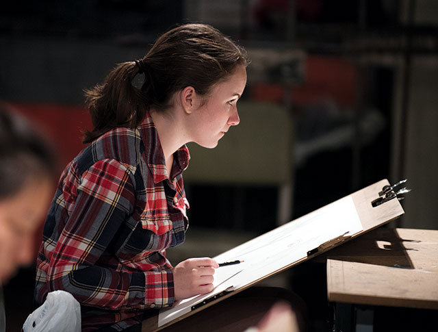 Meghan Johnson, a third-year graphic design student, sketches a classmate in an art course.