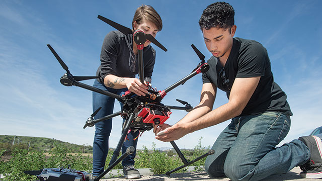 Katrina Nordyke and Andrew Rashid prepare a hexicopter for an aerial survey art Spadra Farm - a research project in which they assessed the color of the crop to determine the effectiveness of the fertilizer and irrigation.