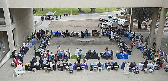 Staff members wander from table to table at the Benefits and Wellness Fair in the CLA Paseo.