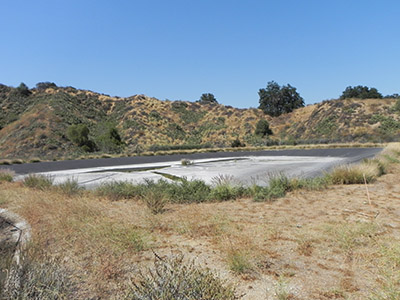 The 2-million-gallon reservoir of reclaimed water for crop irrigation and landscaping sits on a plateau overlooking Parking Lot M.