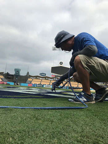 Oscar Del Real paints the logo on the field.