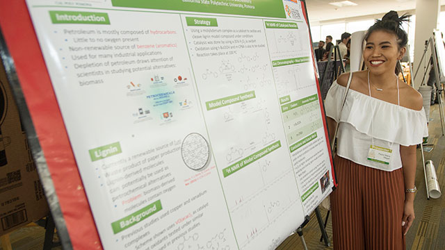 Paula Magat with her poster about her research on Molydbednum-Catalyzed Oxidative Cleavage of Lignin at the Creative Activities and Research Symposium.