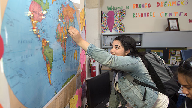 Students use pins to mark the country they identify with during the Dreamers Resource Center open house.