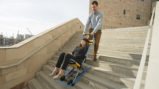 Clay Fowler and Natalie Noyes demonstrate the use of the emergency evacuation chair on the stairs of the CLA building.