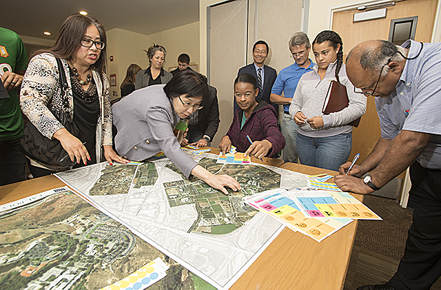 Faculty and staff place stickers on an aerial map of campus on areas that are in need of improvement during Master Plan Workshop at Cal Poly Pomona.