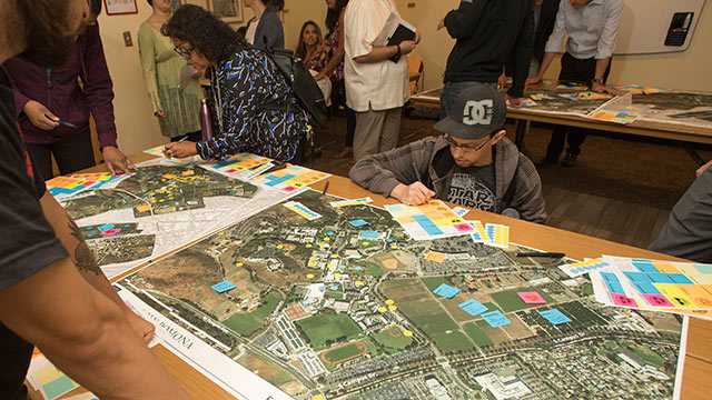 Attendees at the second of a series of open workshops in the Campus Master Plan process write comments that will be placed on large maps of the campus.