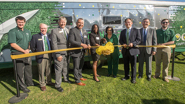Cal Poly Pomona President Soraya M. Coley, Theresa Price of NCRF, engineering professors, students, and local leaders celebrate the expansion of the university's rocketry program by unveiling the new Mobile Operation Center Assembly Trailer to be used for rocketry field work.