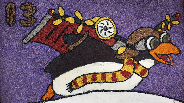 "This ""hidden"" penguin, honoring the 2013 float, was created with dried seaweed (black on penguin's wings), onion seed (black thin lines) dried cranberry seeds (red), dried marigold petals (orange and yellow), flax seed (brown), rice powder (white), dried parsley (green), dried static petals (purple back ground and pink), and a mixture of rice powder and onion seed (grey)."