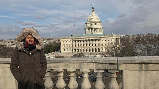 Student Veteran Mayra Chan stands on a balcony in front of the U.S. Capitol Building in Washington, D.C.