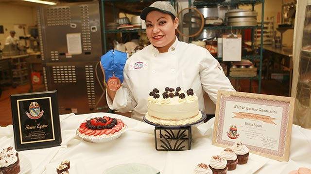 Chef Fionna Espana, in the Los Olivos kitchen, with her medal for being named Pastry Chef of the year by the Chef de Cuisine Association and some of the dining hall's desserts.