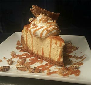 Chef Fionna Espana's fresh pumpkin cheesecake topped with drizzled caramel and pecans.