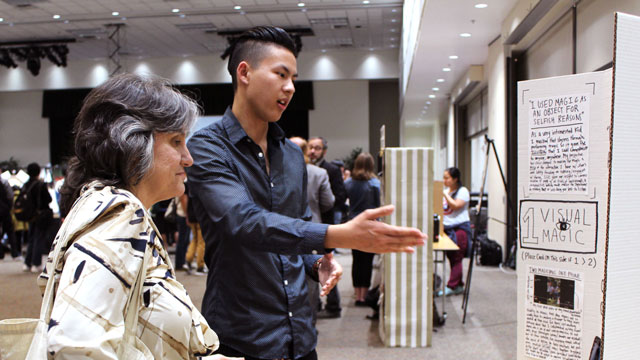 IGE student Kevin Li, a practicing magician, discusses his project with Professor Rosanne Welch.