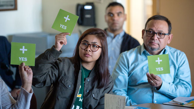 Participants at a Campus Master Plan sustainability workshop use signs to reply to a question during a hands-on exercise.