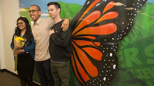 Mike Pedro, coordinator of the Dreamer's Resource Center, stands with mural artists Mirian Estrella and Thomas Louis Dwyer-Gutierrez in front of the work, Dreams with no Borders.