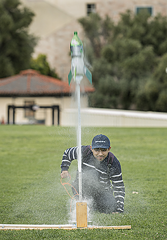 Nirupam Saha launches a water bottle rocket in the Engineering Meadow in preparation for a competition for aerospace majors at Cal Poly Pomona.