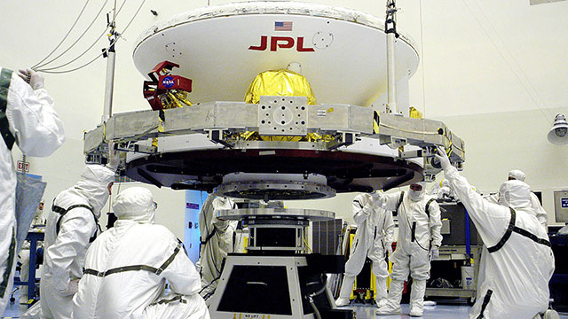 "Engineers work on Opportunity (in its cruise configuration) in a cleanroom at Kennedy Space Center. A very important part of planetary protection is keeping contaminants from humans from riding aboard spacecraft. The pictured engineers are donning ""bunny suits"" that only allow their eyes to be exposed."