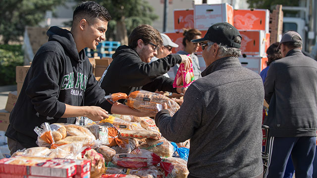 Jason Martinez helps distribute bread during a Sowing Seeds For Life Food Pantry in La Verne May 16, 2018.