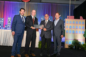 Mike Biagi (second from left), director of CPP Parking & Transportation Services, and Bruyn Bevans, senior project manager for Parking Structure 2, hold the Award for New Sustainable Parking & Transportation Facilities Excellence from the International Parking Institute. They are flanked by Trevyr Meade, certification program lead, and John Schmid, CEO of Propark.
