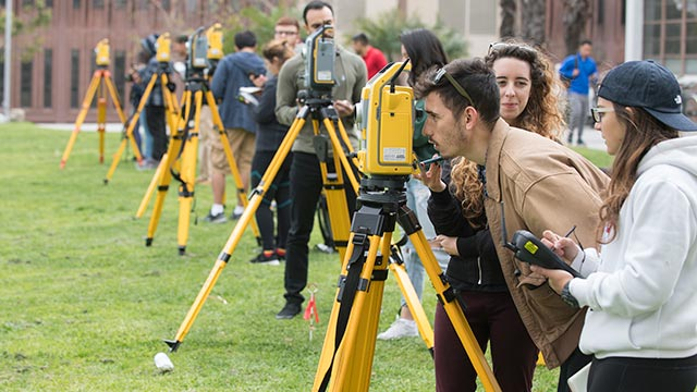 Students take measurements during their advanced surveying course in the Engineering Meadow.