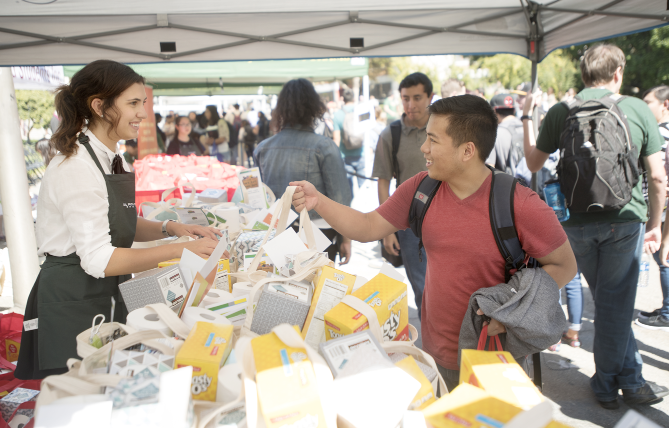 Political Science Major Juliet Wander helps distribute bags of donated food to students.