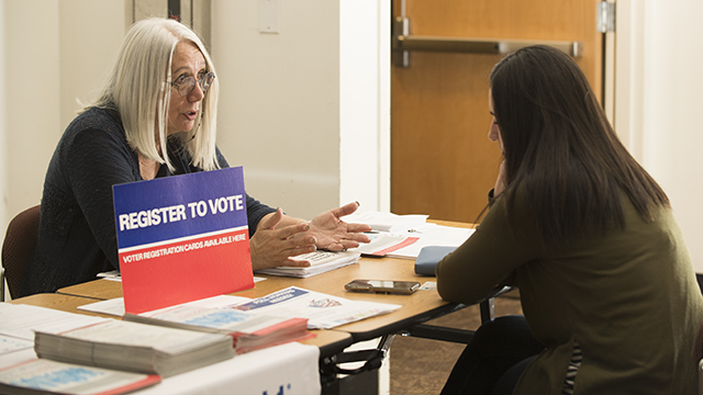 Cindy Reul of the League of Women Voters talks a student through the process of registering to vote during the Election Fair.