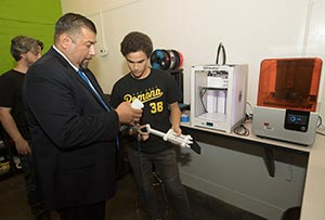 Student showing Pomona Unified Superintendent Richard Martinez 3D-printed models in the Printing Lab.