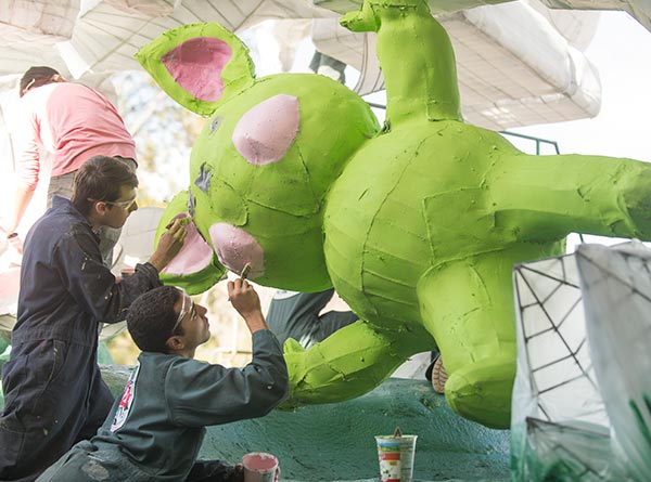 Students paint an alien on the 2019 Cal Poly Universities Rose Float, Far Out Frequencies.