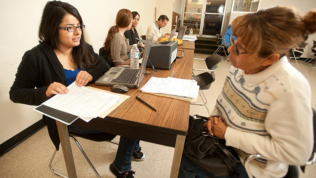 Accounting major Natalie Garduno helps Concepcion Rivera with her income tax preparation.