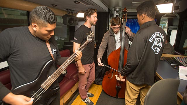 Students and staff work on a song in the John Lennon Bus.