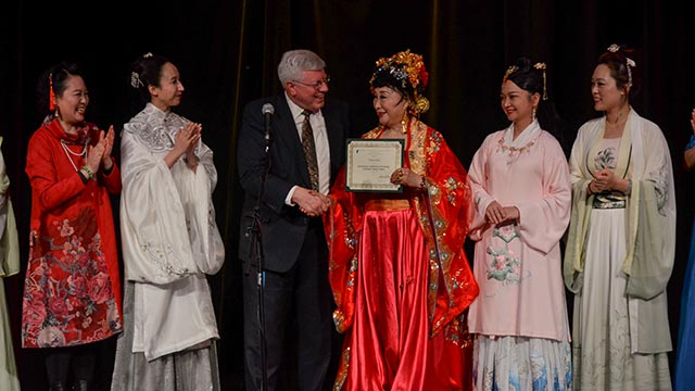 Howard E. Evans, dean of the College of the Extended University and International Center, awards a certificate of appreciation to Professor Wang Sufen, the performing troupe leader of the China Conservatory of Music.