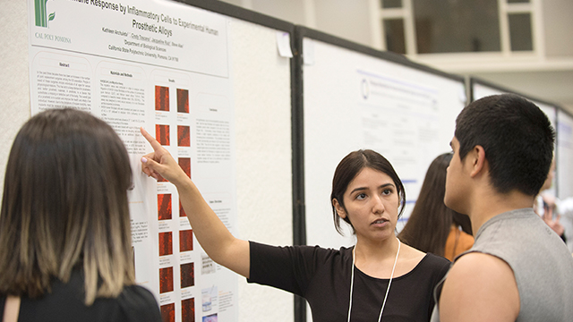 "Jacqueline Ruiz, a senior majoring in microbiology explains her research team's work and results on the project ""Prosthetic Alloys-Immune Response by Inflammatory Cells to Experimental Human Prosthetic alloys"" during the poster session for the 7th Annual Research, Scholarship and Creative Activities Conference."
