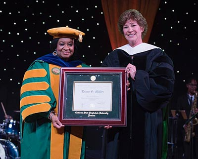 CPP alumna Diane Miller and President Coley hold the honorary doctorate awarded to Ms. Miller Saturday night.