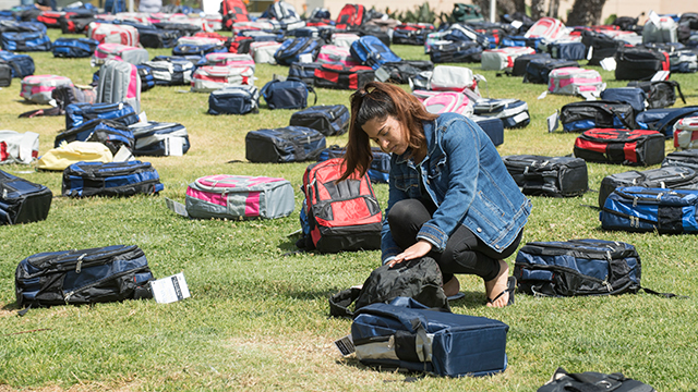 Sanika Gavankar looks over backpacks representing suicides in University Park as part of Send Silence Packing exhibit.