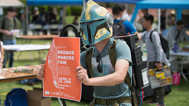 Tucker Dunbar tries to recruit passersby to the Bronco Makers Fair while wearing a Star Wars helmet and a Ghostbusters Proton Pack.